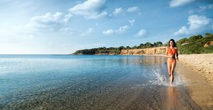 A menina bonita no biquini está correndo na praia fotos de stock royalty free