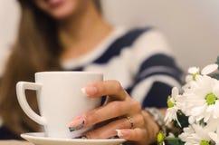 A menina bonita no café com flores bebe o café Fotos de Stock Royalty Free