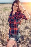 Menina bonita no campo moreno, com o cabelo moreno longo, relaxando na natureza, close-up Corrige o cabelo Conceito Foto de Stock