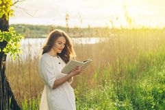Menina bonita no campo que l? um livro A menina que senta-se em uma grama, lendo um livro Resto e leitura imagens de stock royalty free