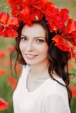 Menina bonita no campo vermelho da papoila fotografia de stock royalty free