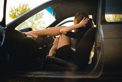 A menina bonita no carro pôs seus pés sobre o painel fotos de stock royalty free