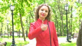 A menina bonita no casaco de cabedal vermelho sorri e mostra o polegar acima O gesto gosta, recomenda video estoque