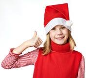 Menina bonita no chapéu de Santa com os polegares acima da aprovação do sinal isolados Fotos de Stock Royalty Free
