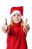 Menina bonita no chapéu de Santa com os polegares acima da aprovação do sinal isolados Foto de Stock