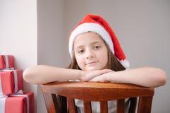 Menina bonita no chapéu de Santa que senta-se em um sorriso da cadeira imagem de stock