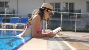 Menina bonita no chapéu e no livro de leitura dos óculos de sol na associação Jovem mulher que relaxa no dia ensolarado morno dur vídeos de arquivo