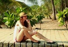 A menina bonita no chapéu está sentando-se em um cais de madeira Fotografia de Stock Royalty Free