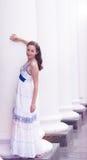Menina bonita no colunas brancas longas Fotografia de Stock Royalty Free