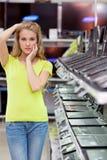 Menina bonita no departamento dos portáteis na loja da eletrônica imagens de stock royalty free