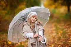 A menina bonita no equipamento do vintage com um guarda-chuva transparente anda no parque do outono, fundo alaranjado foto de stock royalty free