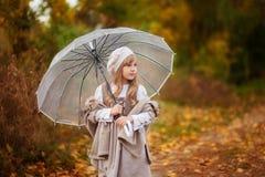 A menina bonita no equipamento do vintage com um guarda-chuva transparente anda no parque do outono, fundo alaranjado imagem de stock royalty free