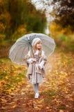 A menina bonita no equipamento do vintage com um guarda-chuva transparente anda no parque do outono, fundo alaranjado fotos de stock royalty free