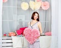 Menina bonita no estúdio colorido da decoração Coração nas mãos Foto de Stock Royalty Free