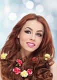 Menina bonita no estúdio com os cravos amarelos e vermelhos em seu cabelo encaracolado Imagens de Stock