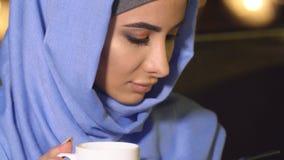 Menina bonita no hijab usando um telefone celular em um café A mulher e as novas tecnologias muçulmanas modernas video estoque