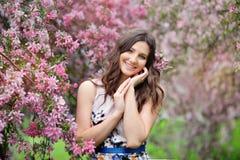 Menina bonita no jardim da mola entre as árvores de florescência Imagem de Stock