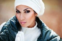 Menina bonita no levantamento branco do chapéu e das luvas fotografia de stock