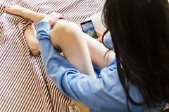 A menina bonita no macacão e nos fones de ouvido da sarja de Nimes está escutando a música usando um telefone esperto e sorrindo  Imagens de Stock