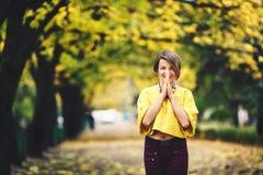 A menina bonita no outono está na aleia com bordos amarelos e guarda suas mãos perto de sua boca com sorriso imagem de stock