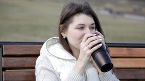 Menina bonita no parque em um café bebendo do banco de uma caneca e na fala no telefone Vista pelos olhos de vídeos de arquivo