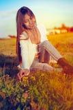 A menina bonita no prado que senta-se na colheita da grama floresce Foto de Stock