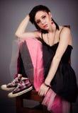 Menina bonita no preto e o vestido e as sapatilhas do rosa que sentam-se em uma cadeira de pernas cruzadas Fotos de Stock