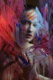 Menina bonita no respingo da pintura da cor atrás da cor pintada de vidro imagens de stock