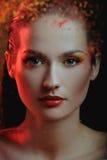 Menina bonita no respingo da pintura da cor atrás da cor pintada de vidro na luz vermelha fotos de stock royalty free