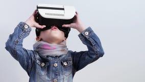A menina bonita no revestimento da sarja de Nimes olha no dispositivo uma realidade virtual Expressão facial do wow video estoque