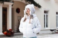 Menina bonita no revestimento do inverno que olha acima perto da casa Imagem de Stock Royalty Free