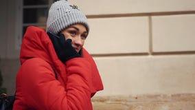 A menina bonita no revestimento vermelho fala no smartphone que está na rua em um dia de inverno brilhante vídeos de arquivo