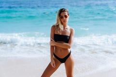 Menina bonita no roupa de banho preto e nos óculos de sol que descansam perto do oceano na praia fotografia de stock