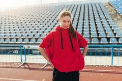 Menina bonita no sportswear que está na pista de atletismo e que prepara-se para correr Aquecimento da manhã antes do exercício fotografia de stock