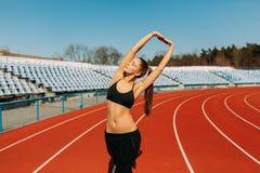 Menina bonita no sportswear que está na pista de atletismo e que prepara-se para correr Aquecimento da manhã antes do exercício foto de stock