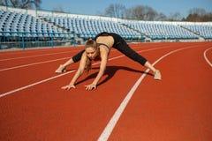 Menina bonita no sportswear que está na pista de atletismo e que prepara-se para correr Aquecimento da manhã antes do exercício fotos de stock royalty free