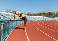 Menina bonita no sportswear que está na pista de atletismo e que prepara-se para correr Aquecimento da manhã antes do exercício imagem de stock