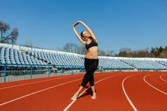 Menina bonita no sportswear que está na pista de atletismo e que prepara-se para correr Aquecimento da manhã antes do exercício fotografia de stock royalty free