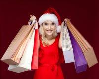 A menina bonita no tampão do Natal entrega pacotes imagens de stock
