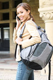 Menina bonita no telefone de pilha na escola Imagens de Stock Royalty Free