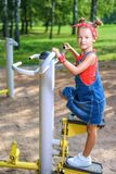 Menina bonita no terno da sarja de Nimes e jogos vermelhos do bandana no campo de jogos das crianças fotografia de stock