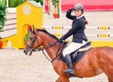 Menina bonita no uniforme e no cavalo do adestramento da baía na competição do showjumping Foto de Stock Royalty Free