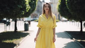 Menina bonita no vestido amarelo que anda ao longo da cidade da rua da rua Mulher borrada da luz do sol do verão do dia ensolarad video estoque