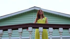 A menina bonita no vestido amarelo vai no balcão e guardou os trilhos video estoque