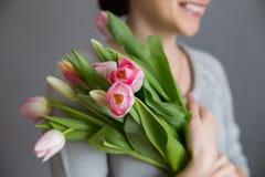 Menina bonita no vestido azul com as tulipas das flores nas mãos em um fundo claro Fotografia de Stock Royalty Free