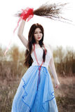 Menina bonita no vestido azul longo com tira vermelha Fotografia de Stock