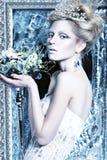 Menina bonita no vestido branco na imagem da rainha da neve com uma coroa em sua cabeça Fotos de Stock Royalty Free