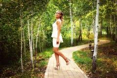 Menina bonita no vestido branco no parque Imagem de Stock Royalty Free