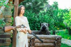 Menina bonita no vestido branco que levanta com um rifle de caça fotografia de stock