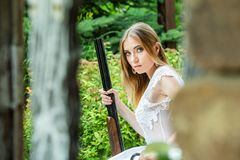Menina bonita no vestido branco que levanta com um rifle de caça fotografia de stock royalty free
